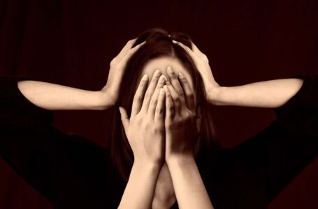 A girl put hands on head and on face due to Migraine headache